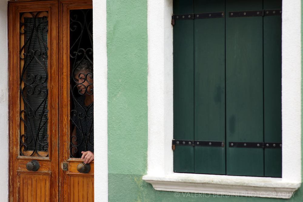 A local woman glances through the door of her home in Burano. Part of the Venetian lagoon the island is famous for its bright painted houses.