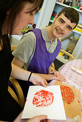 Day Service Assistant chatting to a Day Service users with learning disabilities about the print they have produced in an arts and crafts session,