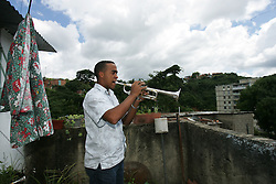 Wilfrido Galarraga, 21,plays his trumpet on the roof of his home in La Vega, a poor shanty town on the outskirts of Caracas, Venezuela.  Wilfrido is part of the Venezuela Simon Bolivar Youth Orchestra, which is part of a music program encompassing more than 200,000 Venezuelan youth.  The program is meant to help underprivileged youth.