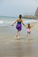 Mother and daughter skipping on beach