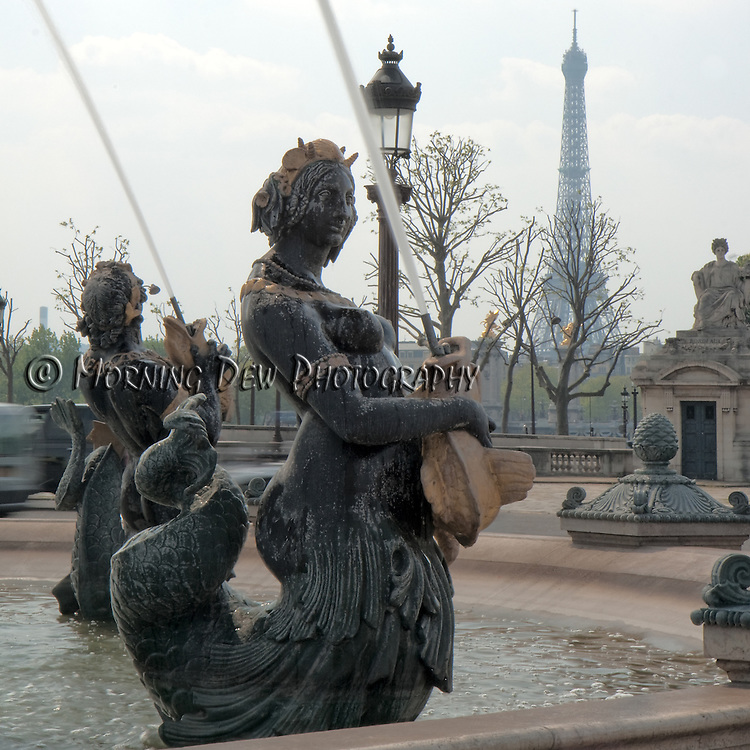 Water sprays from a mermaid fountain in the Place de la Concorde, while the Eiffel Tower looms in the background.