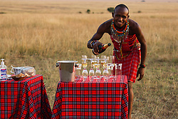 Champagne in the Masai Mara served by a Masai in traditional clothes,