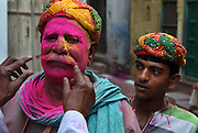 A local man is smeared with pink powder and blessed outside Krishna Temple of Shriji, at Nangdaon, in a counterpart festival to the one held in Barsana on the previous day. The spectacle is a riot of colour amidst frenzied celebrations.