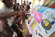 Community members discuss about good hygiene practices to verify how they've understood key messages during a meeting in the village of Kawejah, Grand Cape Mount county, Liberia on Friday April 6, 2012. As part of the UNICEF sponsored CLTS programme, communities learn to put in practice good hygiene and sanitation practices.
