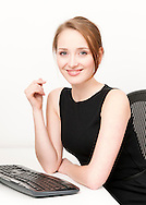 attractive young redhead businesswoman smiling at her desk