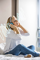 Relaxed mid adult woman enjoying music on headphones in bedroom