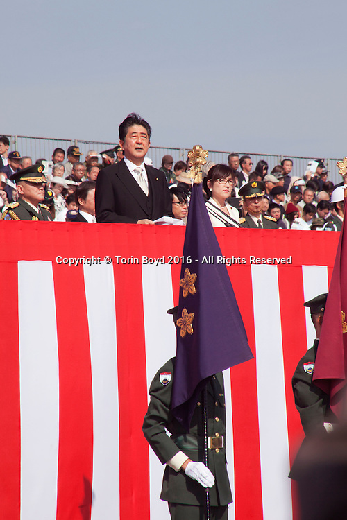 """October, 23, 2016, Asaka, Saitama Prefecture, Japan: Japanese Prime Minister Shinzo Abe proudly reviews his nation's military might during an annual review of the Japan Self Defense Force (JSDF), held at the Asaka Training Area on the outskirts of Tokyo. For this event, PM Abe, top ranking Japanese brass and international dignitaries were in attendance to view Japan's military prowess. This included 4000 troops, 27 divisions, 280 vehicles and artillery, plus 50 aircraft of the Ground, Air, and Maritime branches of the JSDF. Since the post WW II era, Japan has been a pacifist nation with it's constitution drafted by the Allied Occupation in 1947. But Since PM Shinzo Abe took office in 2012, he's had an agenda to revise the constitution which would permit Japan greater autonomy outside it's borders. In December 2013, Abe announced a five year plan of military expansion described as """"proactive pacifism"""", with the goal of making Japan """"a more normal country"""", able to defend itself. This was in reaction to China's buildup of it's military and territorial disputes with Japan, as well as a decreased American influence in the region. This is also a matter of national pride as Japan has been trying to wash away it's past aggressions of WW II. (Torin Boyd/Polaris)."""