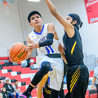 Laguna Acoma Hawk Kevin Martin (11) attempts a layup around a Kirtland Central Bronco during the Eddie Peña Invitational basketball tournament in Grants Thursday.