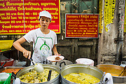 11 SEPTEMBER 2013 - BANGKOK, THAILAND:  A worker serves customers at a curry stand in the Chinatown section of Bangkok. Thailand in general, and Bangkok in particular, has a vibrant tradition of street food and eating on the run. In recent years, Bangkok's street food has become something of an international landmark and is being written about in glossy travel magazines and in the pages of the New York Times.        PHOTO BY JACK KURTZ