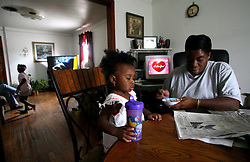 09 July 2006. New Orleans. Louisiana. <br /> Finding Faith. <br /> Faith Figueroa. A day in the life of. Faith sits with her mother Miriam as she scans the local paper for employment opportunities.<br /> Following a ten month search for the little girl whose face appeared on the Sept 19th, 2005 cover of Newsweek magazine, Faith's mother, Miriam Figueroa has returned to town with her three children. Faith, (1 yrs), Anfernya (5yrs) and Jacquelyn (13 yrs). <br /> Credit; Charlie Varley/varleypix.com