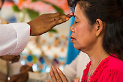 "29 SEPTEMBER 2012 - NAKORN NAYOK, THAILAND:   Brahman priests anoint Thai Buddhists during observances of Ganesh Ustav at Wat Utthayan Ganesh, a temple dedicated to Ganesh in Nakorn Nayok, about three hours from Bangkok. Many Thai Buddhists incorporate Hindu elements, including worship of Ganesh into their spiritual life. Ganesha Chaturthi also known as Vinayaka Chaturthi, is the Hindu festival celebrated on the day of the re-birth of Lord Ganesha, the son of Shiva and Parvati. The festival, also known as Ganeshotsav (""festival of Ganesha"") is observed in the Hindu calendar month of Bhaadrapada, starting on the the fourth day of the waxing moon. The festival lasts for 10 days, ending on the fourteenth day of the waxing moon. Outside India, it is celebrated widely in Nepal and by Hindus in the United States, Canada, Mauritius, Singapore, Thailand, Cambodia, Burma , Fiji and Trinidad & Tobago.    PHOTO BY JACK KURTZ"