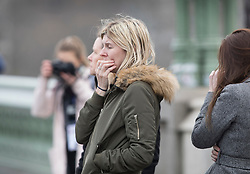 © Licensed to London News Pictures.23/03/2017.London, UK. A woman react after walking along Westminster Bridge to Parliament. A lone terrorist killed 4 people and injured several more, in an attack using a car and a knife at Parliament and on Westminster Bridge yesterday. The attacker managed to gain entry to the grounds of the Houses of Parliament, killing one police officer.Photo credit: Peter Macdiarmid/LNP