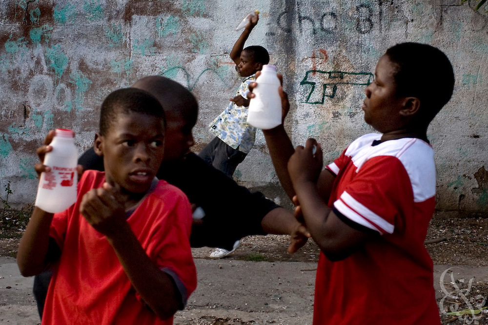 Jamaican boys pretend to have a gang shootout, popping off the lids of juice bottles at one another on a Kingston street June 17, 2008. Children at play in Jamaica often mimmick the environment and the violence that they are surrounded by.  Jamaican boys are disproportionately more likely to fall victim to violence, and often are recruited into gangs as early as age 12.