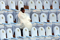 PRETORIA, SOUTH AFRICA - APRIL-27-2004 - A woman claims her seat and waits for the start of the inauguration ceremony for South African President Thabo Mbeki, which marks the 10th Anniversary of the fall of Apartheid in South Africa. (PHOTO © JOCK FISTICK)..<br />