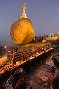 Golden Rock with candles and lights at night, woman taking photo with phone