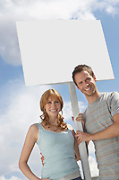Portrait of happy couple with blank sign over cloudy sky