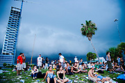 People sat under dark skys at the Vans Warped Tour, USA touring punk rock music festival, Bicentennial park, Miami, Florida, USA. 24th June 2006