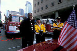Stock photo of two men and a woman standing in front of two firetrucks in downtown Houston Texas