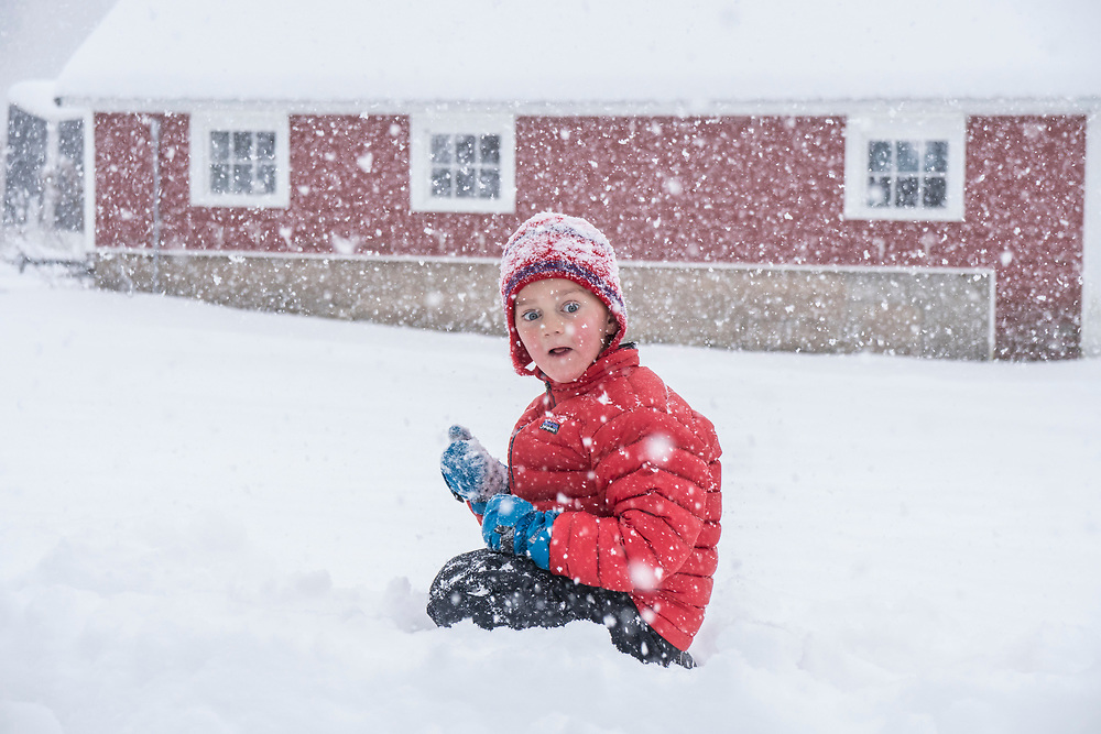 A young boy shovels snow and catches snowflakes during a heavy Lake Superior lake effect snow storm in Michigan.