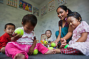 Toddlers sitting on the floor and playing with tennis balls with their teacher, in the Lower Kinder Garden class of a school in Attarkhen, Kathmandu, Nepal. They are children of carpet factory workers, and have been supported into education by GoodWeave, a charity that works towards getting children out of factories and into education.  Previously these children would have been left unattended in the factory while their parents worked as their low salary could not cover childcare costs. GoodWeave were recipients of the Stars Foundation's Impact Award.