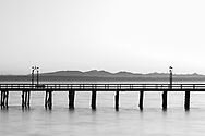 The White Rock Pier in the evening at White Rock, British Columbia, Canada.  Photographed from White Rock Beach looking west across Boundary Bay towards the mountains on Vancouver Island.