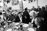 """Torretta, Italy, 17 October 2012: Candidate Francesco Scoma (51) sits at a pizzeria table with mayor of Torretta Vincenzo Guastella (right) and mayor of Monreale Filippo Di Matteo (far right) in Torretta, Italy, on 17 October 2012. Francesco Scoma, a representative of the Sicilian Regional Assembly since 1996, is running for the fifth time at the Regional Parliamento.<br /> <br /> The direct elections in Sicily for the President of the Region and its representatives will take place on Sunday 28 October 2012, 6 months ahead of the end of the terms of office of the current legislature. The anticipated election of October 28 take place after Raffaele Lombardo, former governor of Sicily since 2008, resigned on July 31st. Raffaele Lombardo is under investigation since 2010 for Mafia ties. His son Toti Lombardo is currently running for a seat in the Sicilian Regional Assembly in the coalition of Gianfranco Micciché, a candidate for the Presidency of the Region. 32 candidates belonging to 8 of the 20 parties running for the Sicilian elections are either under investigation or condemned. ### Torretta, Italia, 17 ottobre 2012: Massimo Gargano (destra), un candidato dell'UdC (Unione di Centro) all'Assemblea Regionale Siciliana, stringe la mano agli abitanti locali nella pizzeria """"Da Zia Carolina"""" durante una cena organizzata dai suoi sostenitori a Torretta, Italia, il 17 ottobre 2012.<br /> <br /> Le elezioni in Sicilia per la votazione diretta del presidente della regionee dei deputati all'Assemblea regionale (ARS)si terranno domenica 28 ottobre, in anticipo sulla scadenza naturale dell'attuale legislatura, prevista ad aprile dell'anno prossimo. In Sicilia si vota in anticipo dopo le dimissionidel 31 luglio scorso di Raffaele Lombardo, eletto presidente della regione nell'aprile del 2008 e indagato dal 2010 per concorso esterno in associazione mafiosa. 32 candidati appartenenti a 8 delle 20 liste candidate alle elezioni siciliani sono indagati o condannati."""