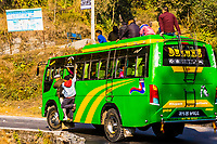 Passengers ride on the roof of a local bus, Pokhara, Nepal.