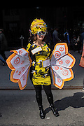 "New York, NY, USA-27 March 2016. A woman wearing a bee costume with two signs on it: ""Bee"" and  ""Happy"" in the annual Easter Bonnet Parade and Festival."