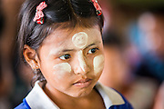 04 MARCH 2014 - MAE SOT, TAK, THAILAND: A Burmese girl with traditional thanaka powder on her face at the Sky Blue School in Mae Sot. There are approximately 140 students in the Sky Blue School, north of Mae Sot. The school is next to the main landfill for Mae Sot and serves the children of the people who work in the landfill. The school relies on grants and donations from Non Governmental Organizations (NGOs). Reforms in Myanmar have alllowed NGOs to operate in Myanmar, as a result many NGOs are shifting resources to operations in Myanmar, leaving Burmese migrants and refugees in Thailand vulnerable. The Sky Blue School was not able to pay its teachers for three months during the current school year because money promised by a NGO wasn't delivered when the NGO started to support schools in Burma. The school got an emergency grant from the Burma Migrant Teachers' Association and has since been able to pay the teachers.    PHOTO BY JACK KURTZ