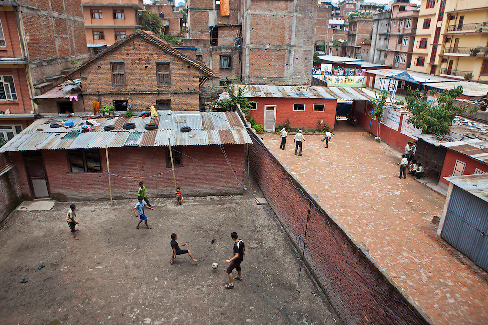 Young Nepalese street-children play football in the back yard of the Voice of Children rehabilitation center in Kathmandu, Nepal. School boys from a private school are also playing football in the yard next door on the right.