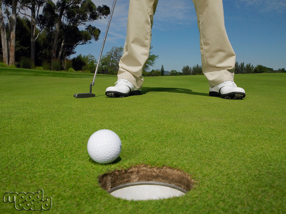 Male golfer standing on green low section ball at hole on foreground