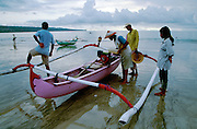 Jimbaran Beach. Fishermen getting their outrigger canoe ready for the evening catch.