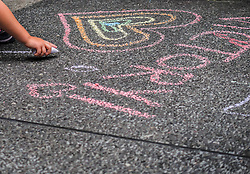 United States, Washington, Seattle Gay Pride Parade, June 28th, 2015. Children at parade drawing on street with colored chalk.
