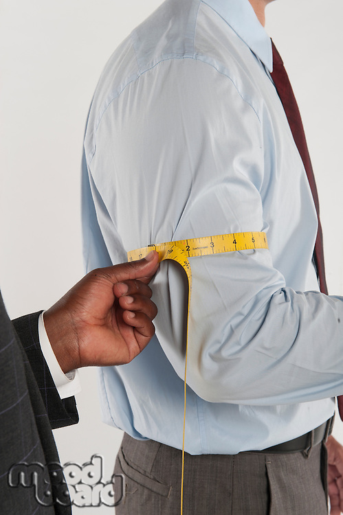 Tailor taking the measurement of a customer