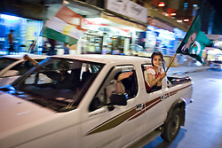 LNP Weekly Highlights 02/05/14. FILE PICTURE. © Licensed to London News Pictures. 27/04/2014. Sulaimaniya, Iraq. A young girl hangs from a car window waving a flag bearing the face of Jalal Talabani, leader of the Patriotic Union of Kurdistan (PUK) political party, during celebrations in the lead up to the 2014 Iraqi parliamentary elections in Sulaimaniya, Iraqi-Kurdistan.<br />