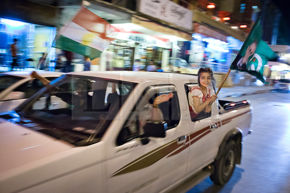 LNP Weekly Highlights 02/05/14. FILE PICTURE. © Licensed to London News Pictures. 27/04/2014. Sulaimaniya, Iraq. A young girl hangs from a car window waving a flag bearing the face of Jalal Talabani, leader of the Patriotic Union of Kurdistan (PUK) political party, during celebrations in the lead up to the 2014 Iraqi parliamentary elections in Sulaimaniya, Iraqi-Kurdistan.<br /> <br /> Although banned in other parts of Iraqi-Kurdistan, the days leading up to an election in Sulaimaniya sees political supporters of all the three main parties parading up and down the main street of the city, waving flags, honking horns, letting off fireworks and firing pistols and rifles into the air.<br /> <br /> The period leading up to the elections, the fourth held since the 2003 coalition forces invasion, has already seen six polling stations in central Iraq hit by suicide bombers causing at least 27 deaths. Photo credit: Matt Cetti-Roberts/LNP