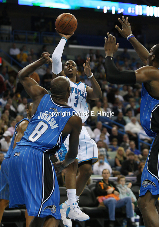 18 February 2009: New Orleans Hornets guard Chris Paul (3) shoots over Orlando Magic defenders Anthony Johnson (8) and Dwight Howard (12) during a NBA basketball game between the Orlando Magic and the New Orleans Hornets at the New Orleans Arena in New Orleans, Louisiana.