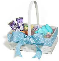 Easter basket with candy inside photographed on a white background