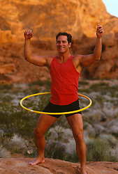 Young man in the desert exercising with a hula hoop
