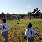 Young outfielders field the ball during the Norwalk Little League baseball competition at Broad River Fields,  Norwalk, Connecticut. USA. Photo Tim Clayton
