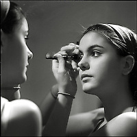 A young woman applying makeup in a mirror