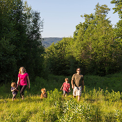 A couple and their two young sons walk in a field in Duxbury, Vermont.
