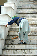 India, Manikaran the Parvarti Valley Kullu District, Himachal Pradesh, Northern India, A woman sweeping the steps of the Hindu temple