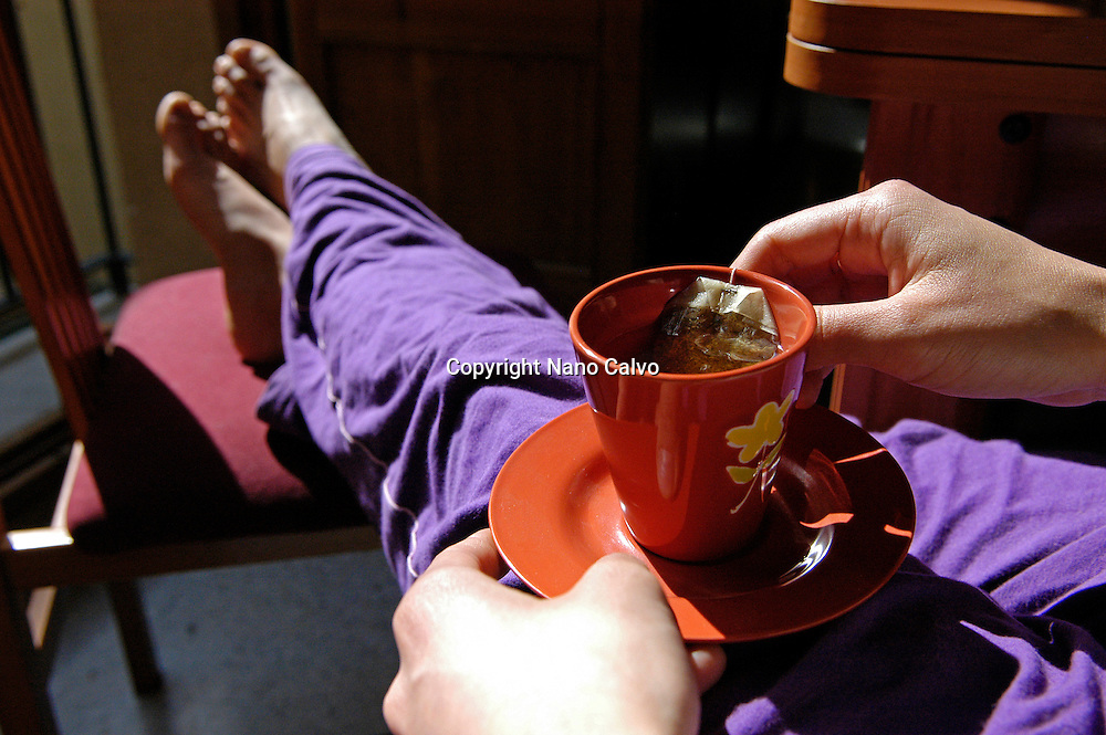 Young woman relaxed, drinking an infusion in the morning