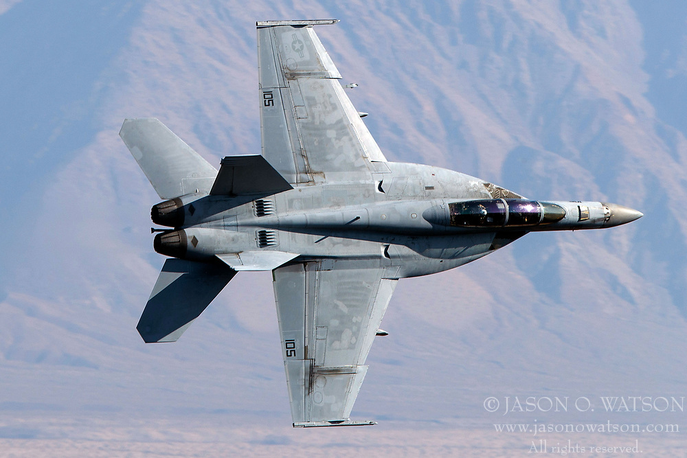 United States Navy Boeing F/A-18F Super Hornet (NE 105) from the VFA-2 Bounty Hunters squadron, Naval Air Station Lemoore, flies low level on the Jedi Transition through Star Wars Canyon / Rainbow Canyon, Death Valley National Park, Panamint Springs, California, United States of America
