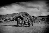 """Kichwa children engage in calisthenics with their teacher outside of their thatched-roof school house in the morning high up where the """"paramo"""" grassland meets the desert-like """"arenal"""" on a high 4,100m (13,451ft) pass near Chimborazo Volcano that separates the altiplano high plateau heartland of Ecuador from the steamy Pacific Coast."""