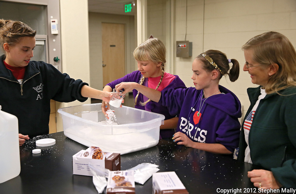 Coe College freshman Kylie Baily (from left) of Marion gives Tracie Martinson, 11, Julie Holt, 11, and Judie Martinson, all of Cedar Rapids, a demonstration on how to make snow polymer during the 10th annual Playground of Science at Peterson Hall on the Coe College campus in Cedar Rapids on Thursday, October 25, 2012.