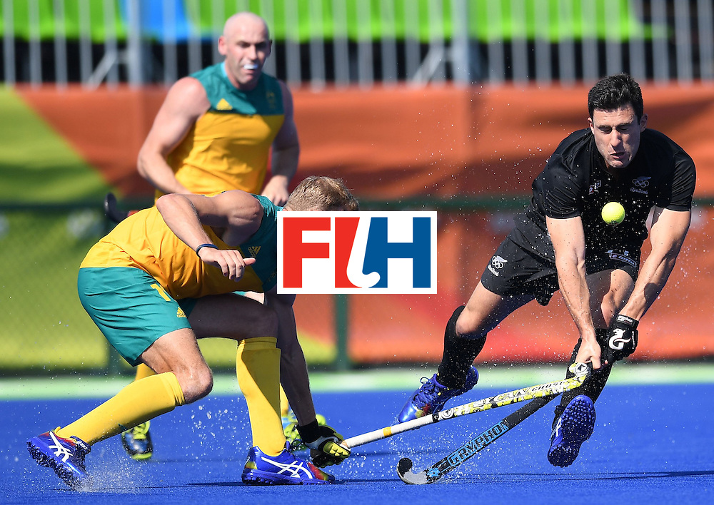 New Zealand's Kane Russell (R) vies for the ball with Australia's Tim Deavin during the men's field hockey Australia vs New Zealand match of the Rio 2016 Olympics Games at the Olympic Hockey Centre in Rio de Janeiro on August, 6 2016. / AFP / MANAN VATSYAYANA        (Photo credit should read MANAN VATSYAYANA/AFP/Getty Images)