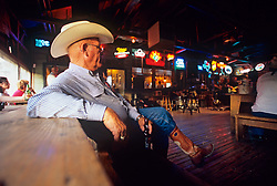 older man in western wear at a bar with a drink