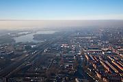 Nederland, Noord-Holland, Amsterdam, 10-01-2009; Oud-Zuid met links de Zuidas (VU, ING), midden Fred. Roeskestraat en begraafplaats Buitenveldert, rechts Rivierenbuurt en Olympisch Stadion; links aan de horizon het water van de Nieuwe Meer met daar achter Schiphol; de lucht laat zogenaamde inversie zien (temperatuuromkering): door het winterweer - met vorst - is er aan het aardopppervlak koude lucht, deze wordt vastgehouden door de dunne warme luchtlaag daar boven; hierdoor ontstaat mist en kan ook ook luchtverontreiniging gevangen gehouden worden (ontstaan smog);.to the left the Zuidas (VU, ING), center Fred. Roeskestraat and cemetery Buitenveldert, right Rivierenbuurt and Olympic Stadium; left on the horizon, the water of the Nieuwe Meer  with  Schiphol airport;.in the air so-called inversion (temperature inversion): cold air on ground level (as a result of to the frosty winter weather), above it a thin warm air layer which prevents the cold air, with fog and pollution, to move upward. .luchtfoto (toeslag); aerial photo (additional fee required); .foto Siebe Swart / photo Siebe Swart